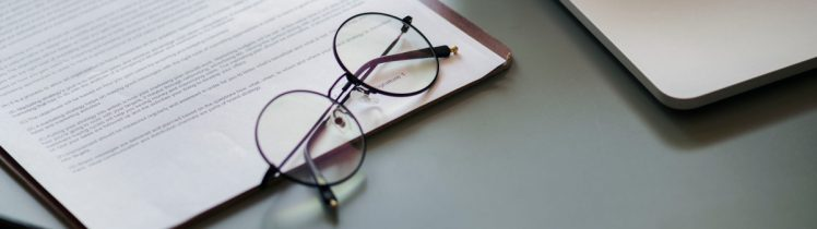glasses on a clipboard with papers on a desk